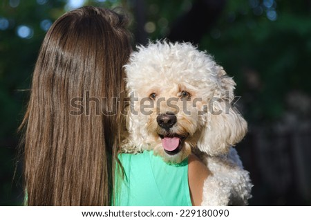 Brown long haired young girl holding her dog on her right shoulder in the forest - stock photo