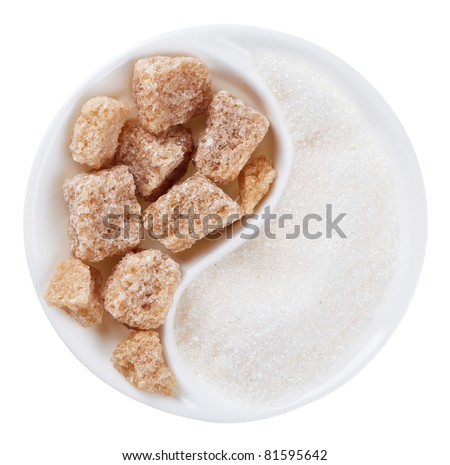 Brown lump cane sugar versus white one in Yang Yin shaped plate, isolated on white - stock photo