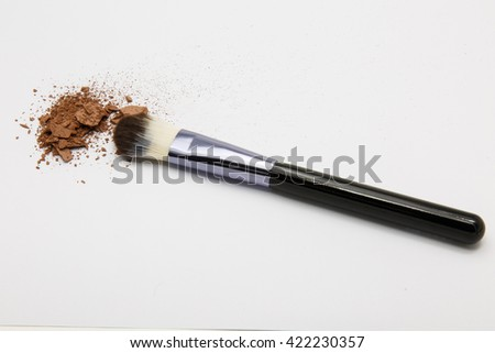 brown makeup powder and brush on white background