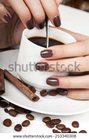 Brown manicure and coffee beans. - stock photo