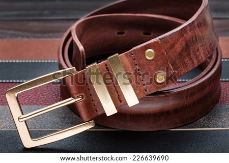 Brown men leather belt with golden buckle over leather strips background - stock photo