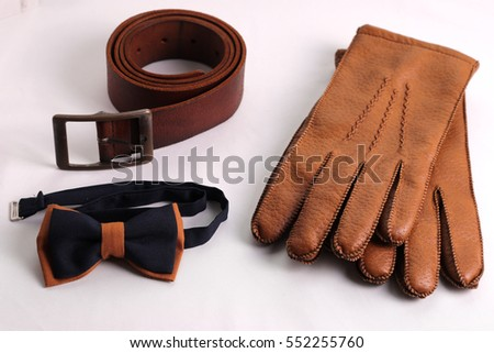 Brown men's accessories, leather gloves, leather belt and tie butterfly. On a white background