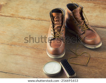 brown men's boots on wooden background