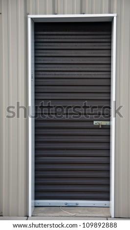 Brown metal door with padlock, of an outdoor storage unit - stock photo