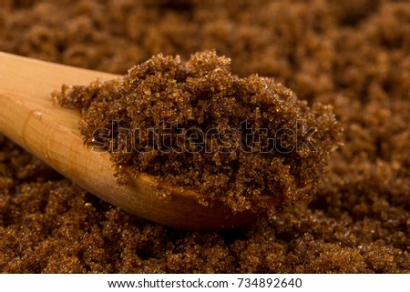 brown muscovado sugar in wooden spoon on the sugar background