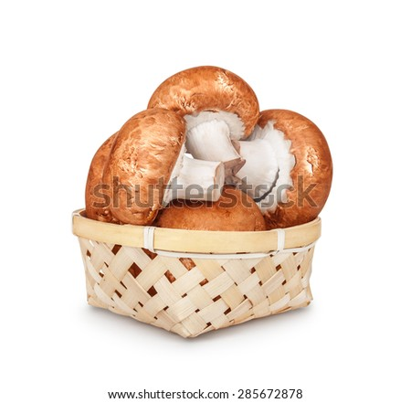 brown mushrooms in a light basket on an isolated white background - stock photo