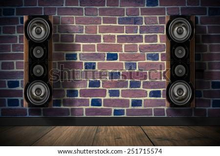 Brown music speakers on brick wall in dark room - stock photo