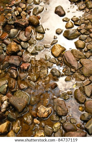 brown natural wet rocks in river water background - stock photo