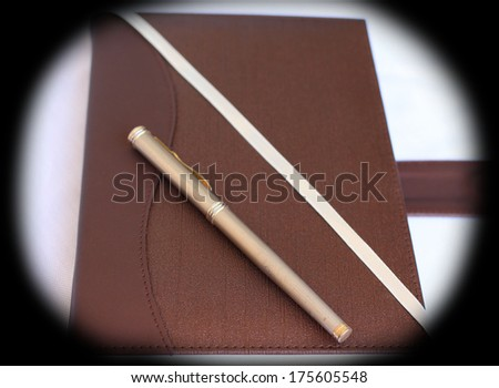 Brown note book and pen on white isolated - stock photo