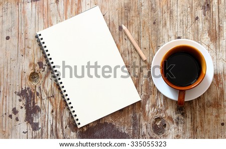 brown note book with coffee cup on grunge wood