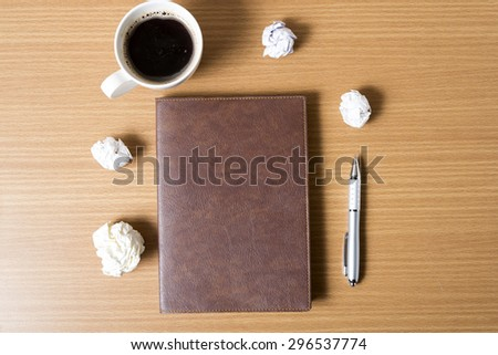 brown notebook and crumpled paper with coffee cup on wood background - stock photo
