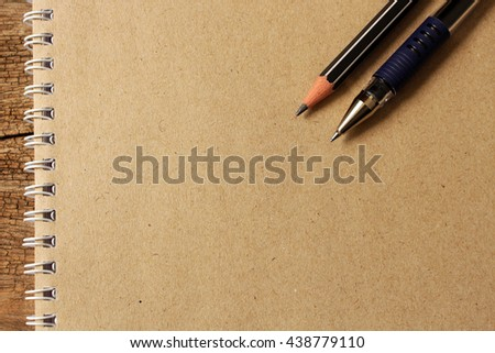 brown notebook paper , pencil and pen on notepaper with empty for text. - stock photo