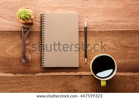 Brown notebook, pencil and cup of coffee on the desk