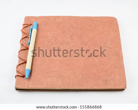 Brown notebook with pen on white background