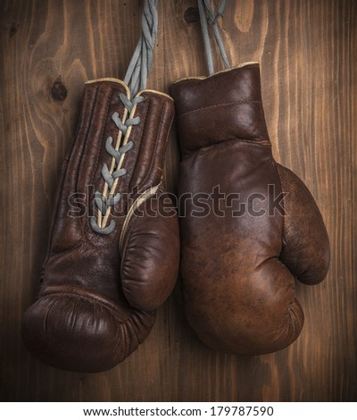 Brown old boxing gloves with a lace over old wooden wall - stock photo