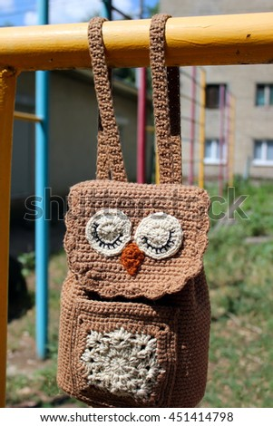 Brown Owl Crochet Backpack for children hanging on the yellow tube. - stock photo