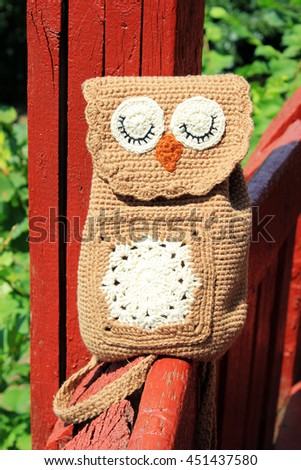 Brown Owl crochet Backpack for children sitting on a red fence. - stock photo