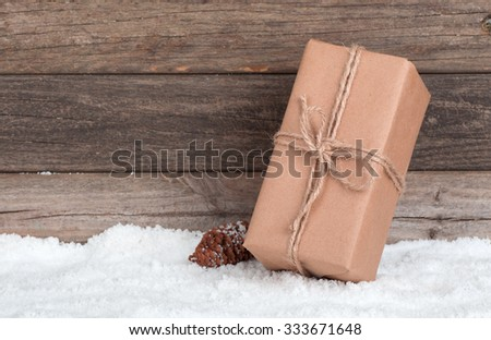 Brown package on snow with wood background