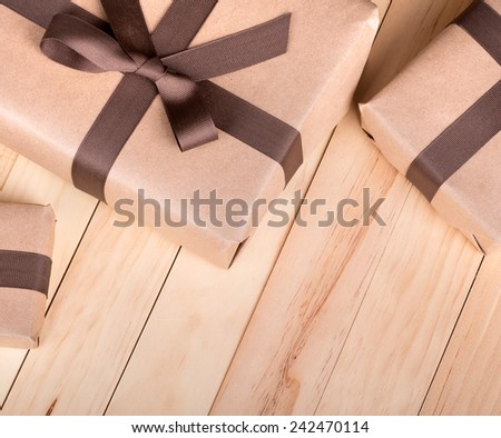 Brown packages wrapped with ribbon and bow on wood surface - stock photo