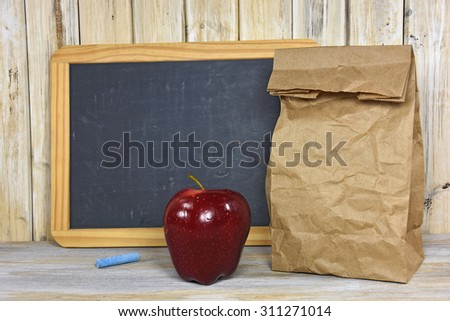 brown paper bag and red apple with black chalkboard on whitewashed wood - stock photo