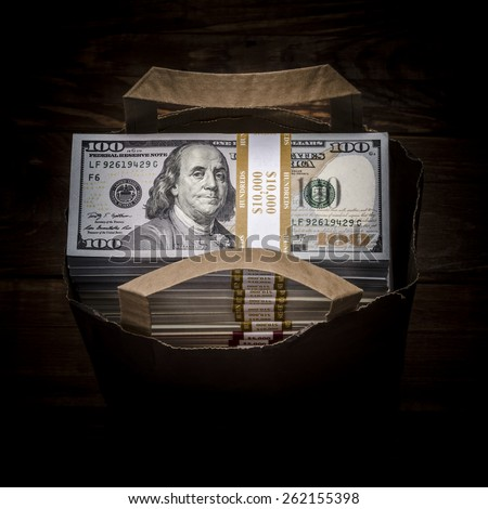 Brown paper bag full of currency. Bag full of money - vintage photography including vignetting effect of brown paper bag full of stacks of hundred dollar bills on wooden background - stock photo