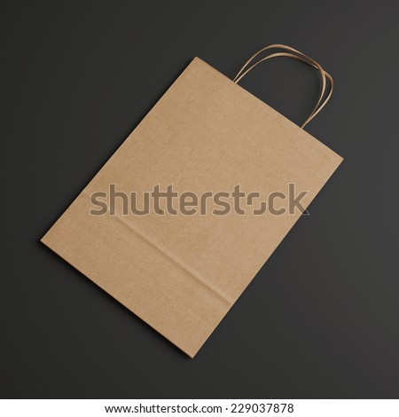 Brown paper bag with handles on dark background - stock photo