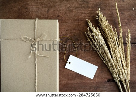 Brown paper box on old wood background with dried flower and copy space, Vintage tone - stock photo