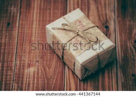 brown paper gift box with text 'love dad' on wooden background, present on father's day