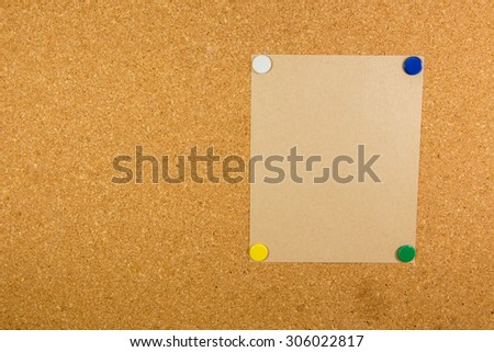 Brown paper on cork board with 4 sticky note pinned
