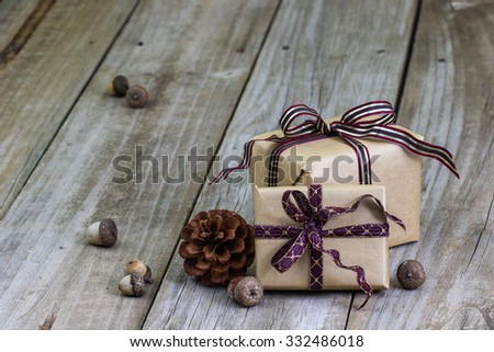 Brown paper packages tied in purple ribbon by acorns and pine cone on antique rustic wooden background - stock photo