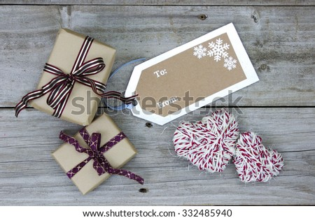 Brown paper packages tied in ribbon by To From tag and rope hearts on antique rustic wooden background; above view - stock photo