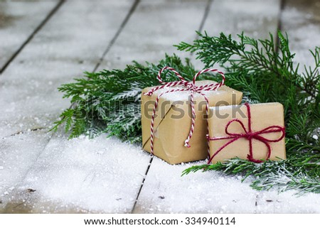 Brown paper packages tied up in string, Christmas tree garland and snow on antique rustic wooden background - stock photo