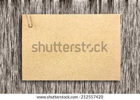 Brown paper sheet on wood texture - stock photo