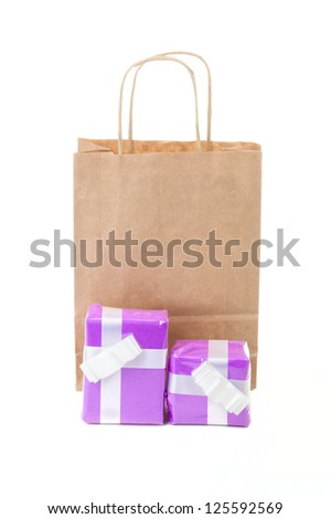 Brown paper shopping bag  with two pink gift boxes isolated on white background
