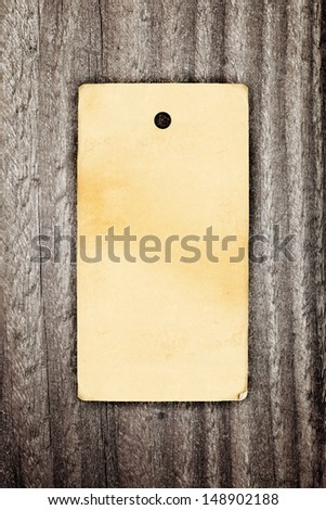 Brown paper vintage clothing label on wooden background - stock photo