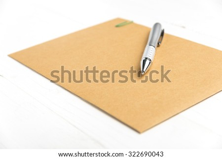 brown paper with pen on white table