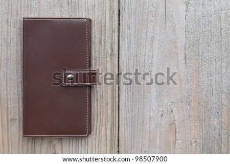 Brown personal notebook on wooden table - stock photo