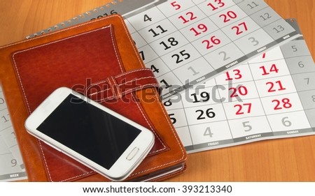 Brown personal organizer or planner with a mobile phone and a calendar on the desktop - stock photo