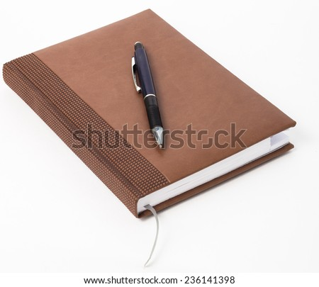brown personal organizer, with pen, on white background. - stock photo