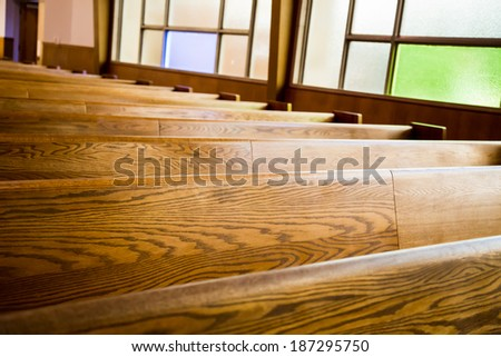 brown pews against stain glass - stock photo