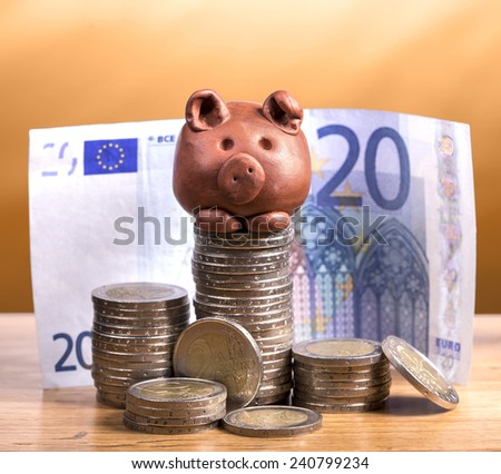 Brown piggy bank and stack of coins with warm gradient background. - stock photo