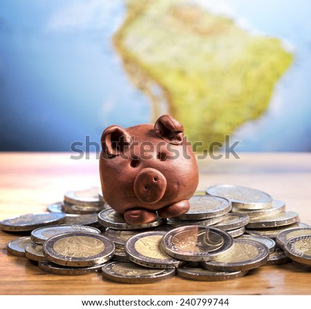 Brown piggy bank sitting on coins with earth background. - stock photo