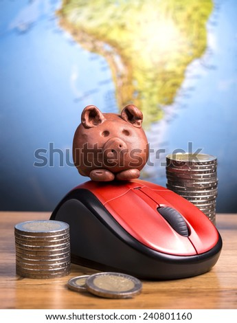 Brown piggy on a computer mouse - stock photo