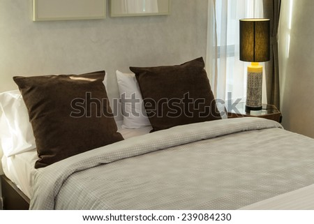 brown pillows on bed with lamp - stock photo