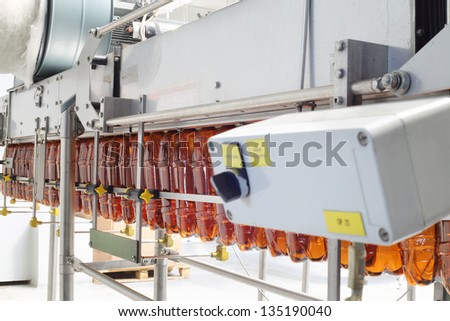 Brown plastic bottles for beer go on conveyor belt at large brewery. - stock photo