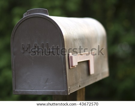 Brown plastic mailbox with a red flag outdoors against a green background. - stock photo