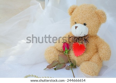 Brown plush Teddy bear with red heart and red rose. Golden like perls on a white wooden surface.