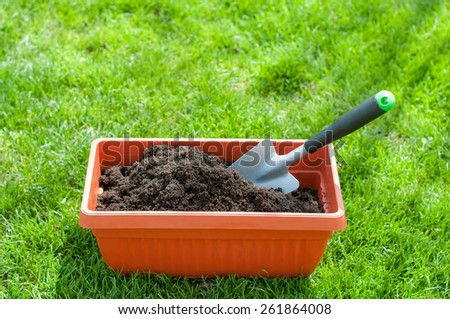 Brown pot with garden shovel and compost - stock photo