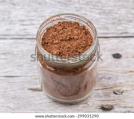 Brown Pure Cocoa Powder In A Mason Jar Over Rustic Wooden Background