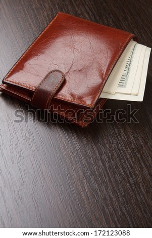 Brown purse on wooden table - stock photo